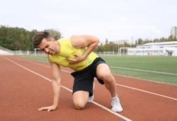Young man having heart attack while running at stadium