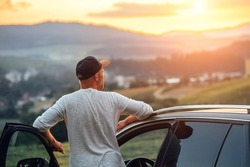 Young man having the long auto trip break. He stoped new car got out of the vehicle and enjoying the sunset orange-pink sky colors.  Traveling by car by the empty nature vastness concept image.