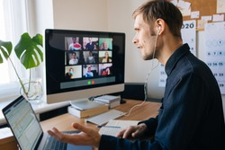 Young man having video call via computer in the home office. Stay at home and work from home concept during Coronavirus pandemic. Virtual house party