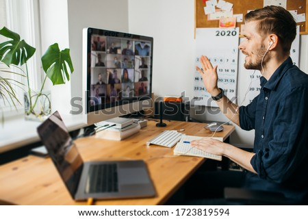 Young man having video conferencing call via computer. Working remotely managing team virtual call  Stay at home and work from home.Virtual House party Home office computer desk.