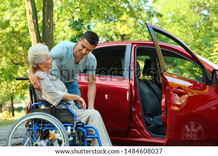 Young man helping disabled senior woman in wheelchair to get into car outdoors #1484608037
