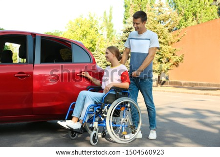 Young man helping disabled woman in wheelchair to get into car outdoors #1504560923