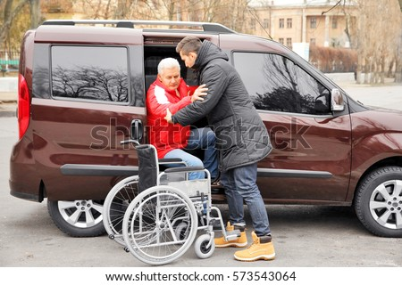 Young man helping handicapped man to sit in wheelchair #573543064