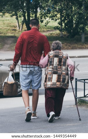 Young man helps old lady with a stick to carry her bag and cross the road
