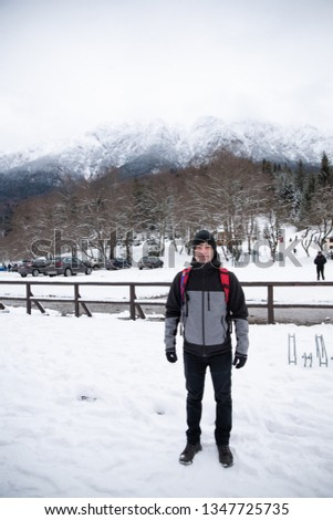 Young man hicking in the mountains during winter in the snow wearing a jacket and carrying a backpack. Active person in the cold weather