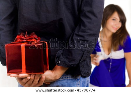 Young man hiding a gift box behind his back