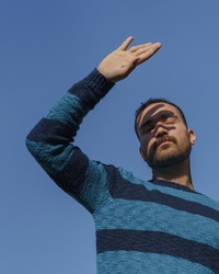 Young man hiding off his face from the sun with his palm