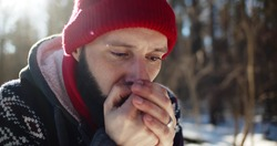 Young man hiker got lost in winter forest and blowing at frozen hands trying to get warm. Portrait of male tourist lost in woods freezing waiting for rescue