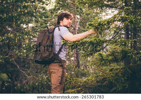 Young Man hiking in forest with backpack Travel Lifestyle and outdoor recreation summer vacations concept