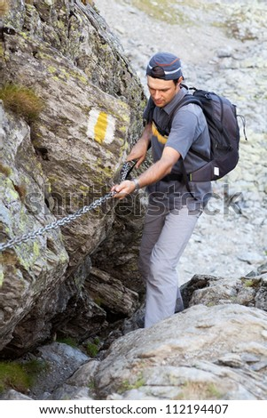 Young man hiking on difficult mountain trail