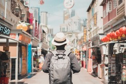 Young man hipster traveling with backpack and hat, happy Solo traveler walking at Chinatown street market in Singapore. landmark and popular for tourist attractions. Southeast Asia Travel concept