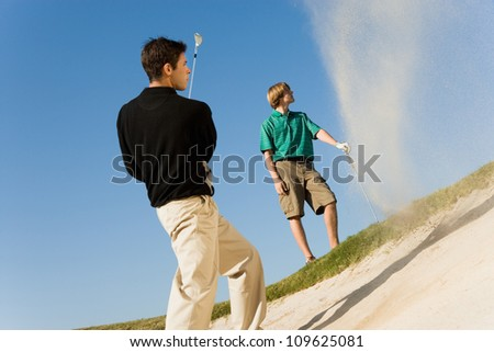 Young man hitting golf ball out of a sand trap with competitor in background