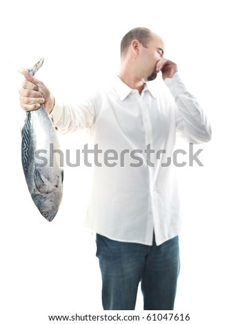 young man hold an smelly fish in his hand selective focus