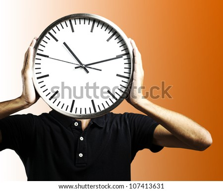 young man holding a big clock covering his face over an orange background