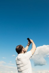 Young man holding a black smartphone in raised hands against a background of blue sky.  There is no mobile signal outside. Search for wi-fi signal. No connection. Looking for a cell signal