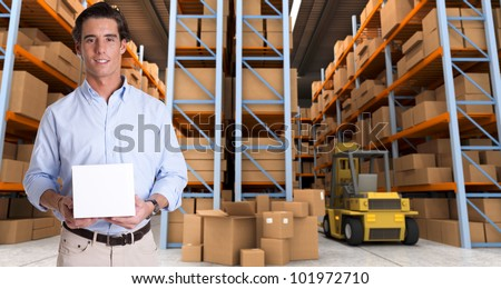 Young man holding a blank white box in a distribution warehouse