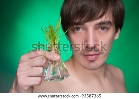 Young man holding a decorative bottle with a bunch of fresh green grass