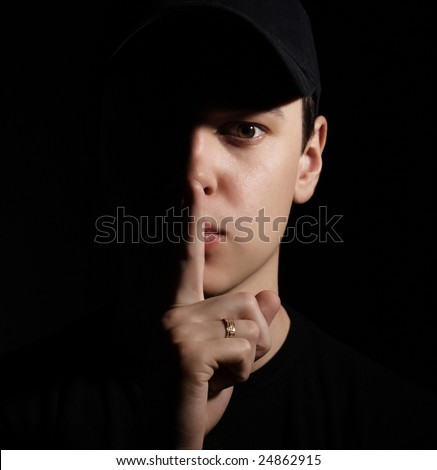 young man holding a finger on his mouth shhh