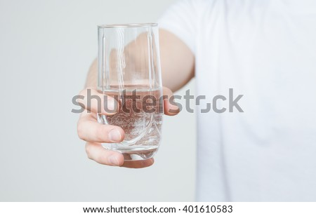 Young man holding a glass with water, closeup shot - Shutterstock ID 401610583
