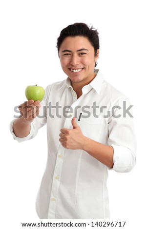 Young man holding a green apple, doing thumbs up. Wearing a white shirt. White background.