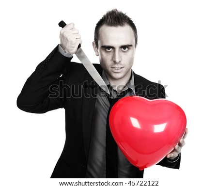 young man holding a heart shaped balloon and a knife - stock photo