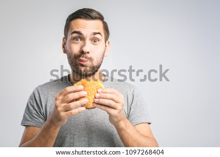 Young man holding a piece of hamburger. Student eats fast food. Burger is not helpful food. Very hungry guy. Diet concept.