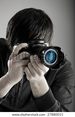 Young man holding a professional DSLR camera and taking pictures