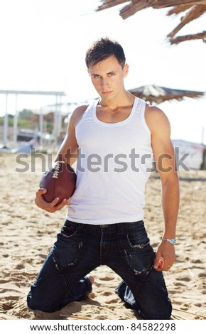 Young man holding a rugby ball with the sea at the background