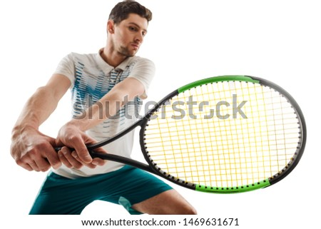 Young man holding a tennis racket after shot. Professional player showing his technique and endurance on a tournament.
