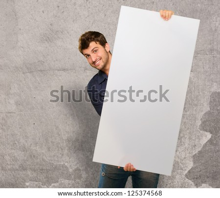 Young Man Holding Banner On Wall