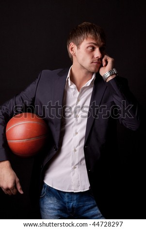 Young man holding basketball ball and celling by the phone