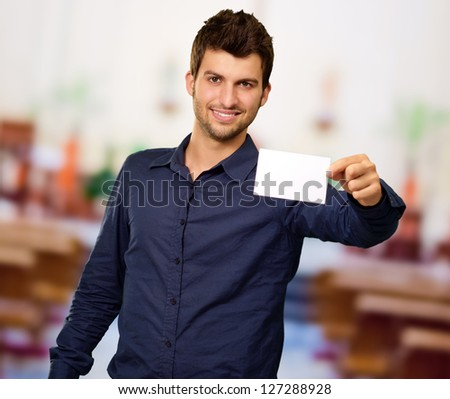 Young Man Holding Blank Visiting Card, Indoors
