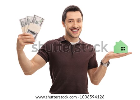 Young man holding bundles of money and a model house isolated on white background