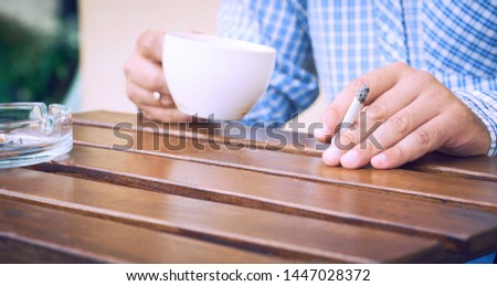 Young man holding cigarette and cup of coffe in hands close-up sitting on the summer terrace of the cafe.