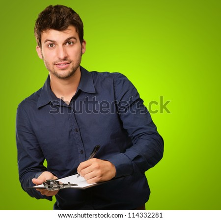 Young Man Holding Clipboard On Green Background