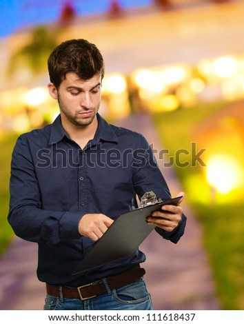 Young Man Holding Clipboard, Outdoor