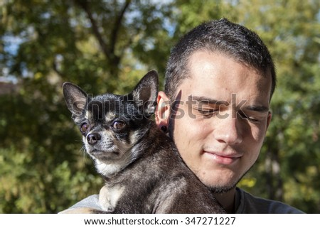 Young man holding cute black chihuahua dog over green nature background
