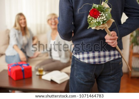 Young man holding flowers bouquet behind the back for his mother. Mother and daughter talking. Mother's day. Happy family moments at home #1071464783