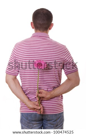 Young man holding gerber flower behind his back