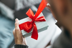 Young man holding gift with red ribbon. Closeup. Opening gift.