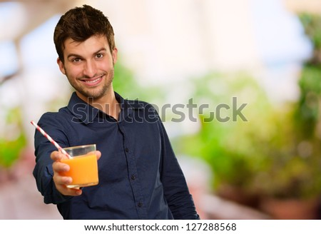 Young Man Holding Glass Of Orange Juice, Outdoors - stock photo