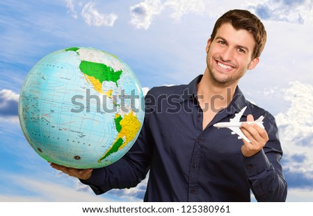 Young Man Holding Globe And Miniature, Outdoors - stock photo