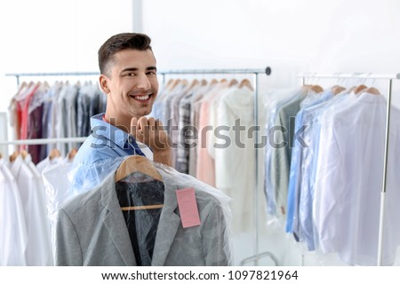 Young man holding hanger with jacket in plastic bag at dry-cleaner's