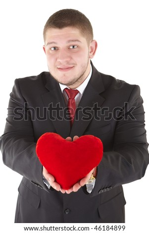 Young man holding heart in his hand. He is giving it somebody. Isolated over white.