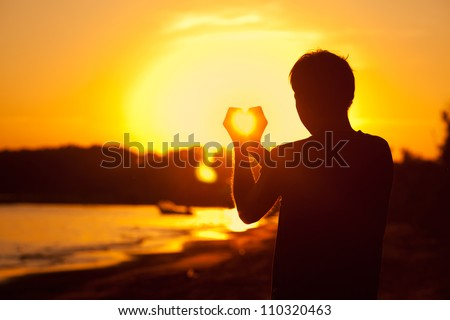 young man holding in hands the setting sun
