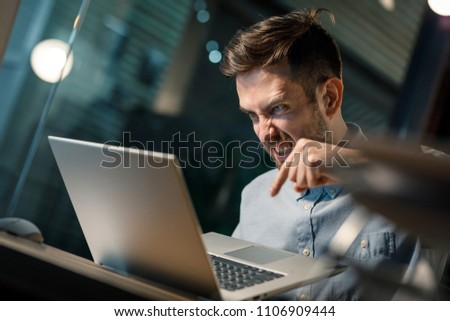 Young man holding laptop and pushing button with anger having problems with gadget work