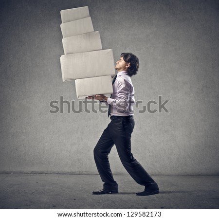 young man holding many heavy boxes
