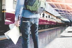 Young man holding map standing on platform at train station for travel. Travel concept by train.