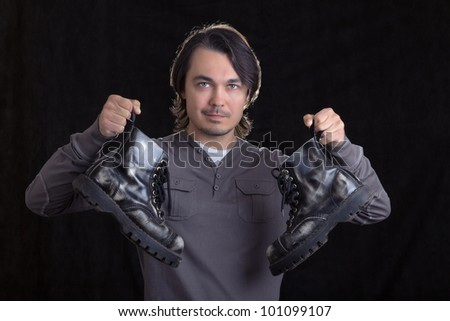 Young man holding old black boots in his hands, on black background