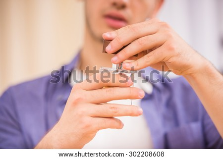 Young man holding perfume in his hands. Close-up.